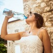 Young woman drinking water out of plastic bottle on street — Stock Photo #58984669