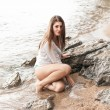 Sexy brunette woman in wet shirt sitting next to big rock at sea — Stock Photo #58985185