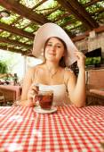 Elegant woman sitting with cup of tea at cafe — Foto Stock