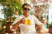 Portrait of handsome man drinking beer at restaurant at hot day — Stock Photo