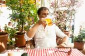 Young man drinking beer at hot day on restaurant summer terrace — Stock Photo