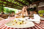 Portrait of overeating woman looking at empty plates on table — Stock Photo