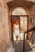 Young woman walking in old forged gates and narrow street — Stock Photo