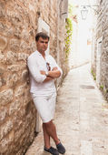 Stylish man leaning against old stone wall on street — Stock Photo