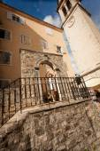 Woman in white hat posing on old stone stairs at city of Budva — Stock Photo