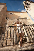 Young woman leaning against metal railings on old stone stairway — Stock Photo