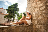 Young woman reading book on tablet on street at sunny day — Stock Photo