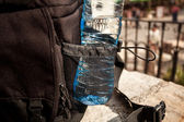 Plastic bottle of water in black backpack — Stock Photo