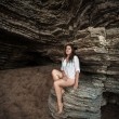 Slim woman sitting on big cliff at sea cave — Stock Photo #59464771
