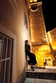 Night shot of woman leaning against old building at street — Stock Photo