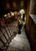 Night shot of woman in dress walking up the stairway on street — Stock Photo