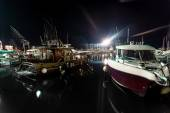 Night shot of wooden and motorboats moored at sea port — Stock Photo