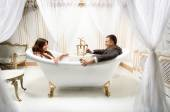 Clothed man and woman having fun in luxurious bath — Stock Photo