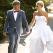Bride and groom holding hands while walking at park — Stock Photo #59667561