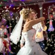 Blonde bride dancing at restaurant in flying confetti — Stock Photo #59667819