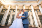 Portrait of happy bride and groom posing against classic buildin — Stock Photo