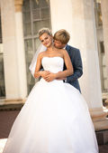 Young groom hugging smiling bride from back on the street — Fotografia Stock
