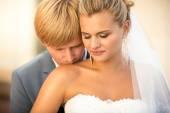 Portrait of handsome groom kissing blonde bride in shoulder — Stock Photo