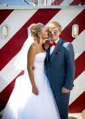 Beautiful bride kissing handsome groom in sunglasses on street — Stock Photo