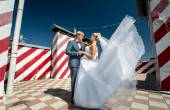 Newly married couple posing on skyscraper roof top at windy day — Stock Photo