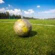 Shabby soccer ball lying on artificial grass field — Stock Photo #61239721
