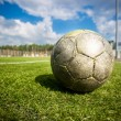 Old soccer ball on grass field at sunny day — Stock Photo #61239827