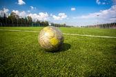 Schäbig Fußball auf Kunstrasen-Feld liegend — Stockfoto