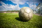 Old soccer ball on grass field at sunny day — Stockfoto