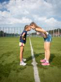 Elder and younger sister standing head to head on grass — Stock Photo
