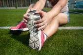 Young woman warming up on grass before running — Stock Photo