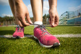 Young woman tying shoe laces before running — Stock Photo