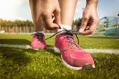 Woman tying laces on sneakers on grass field — Stock Photo