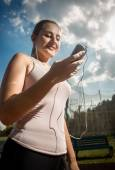 Smiling sporty woman using mobile phone while running — Stock Photo
