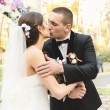 Portrait of happy bride and groom kissing first time at ceremony — Stock Photo #62569959