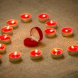Golden ring in box lying inside of heart shape made of candles — Stock Photo #62574703
