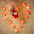 Person holding golden ring in box against heart made of candles — Stock Photo #62574773