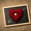 Photo of knitted heart lying on blackboard with drawn arrow — Stock Photo #62575231