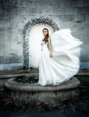 Young bride posing at old castle while wind blows her veil — Stock Photo