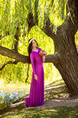Sexy woman in long dress leaning against big tree at riverbank — Stock Photo