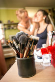 Set of professional makeup brushes against artist doing makeup  — Stock Photo