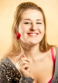 Woman with toothy smile posing with decorative red heart — Stock Photo