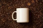 White mug against coffee beans with anise stars lying like steam — Stock Photo