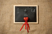 Equation of love written on blackboard with red heart — Stock Photo