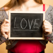 """Portrait of smiling woman holding blackboard with word """"Love"""" — Stock Photo #62638771"""