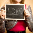 """Beautiful woman holding board with word """"Love"""" written by chalk — Stock Photo #62638795"""
