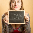 Cute funny woman holding blackboard with word Love — Stock Photo #62638825