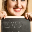 Portrait of smiling woman holding board with two answers — Stock Photo #62639691