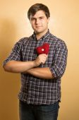 Man in checkered shirt holding decorative red heart — Stock Photo