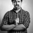 Monochrome portrait of hipster guy posing with fake mustache — Stock Photo #62664063