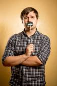 Thoughtful hipster guy posing with fake mustache on stick — Stock Photo